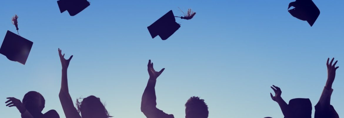 Students celebrating graduation by throwing graduation caps into air
