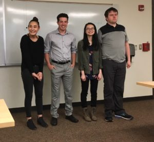 Four young adult students stand at the front of a college classroom smiling.