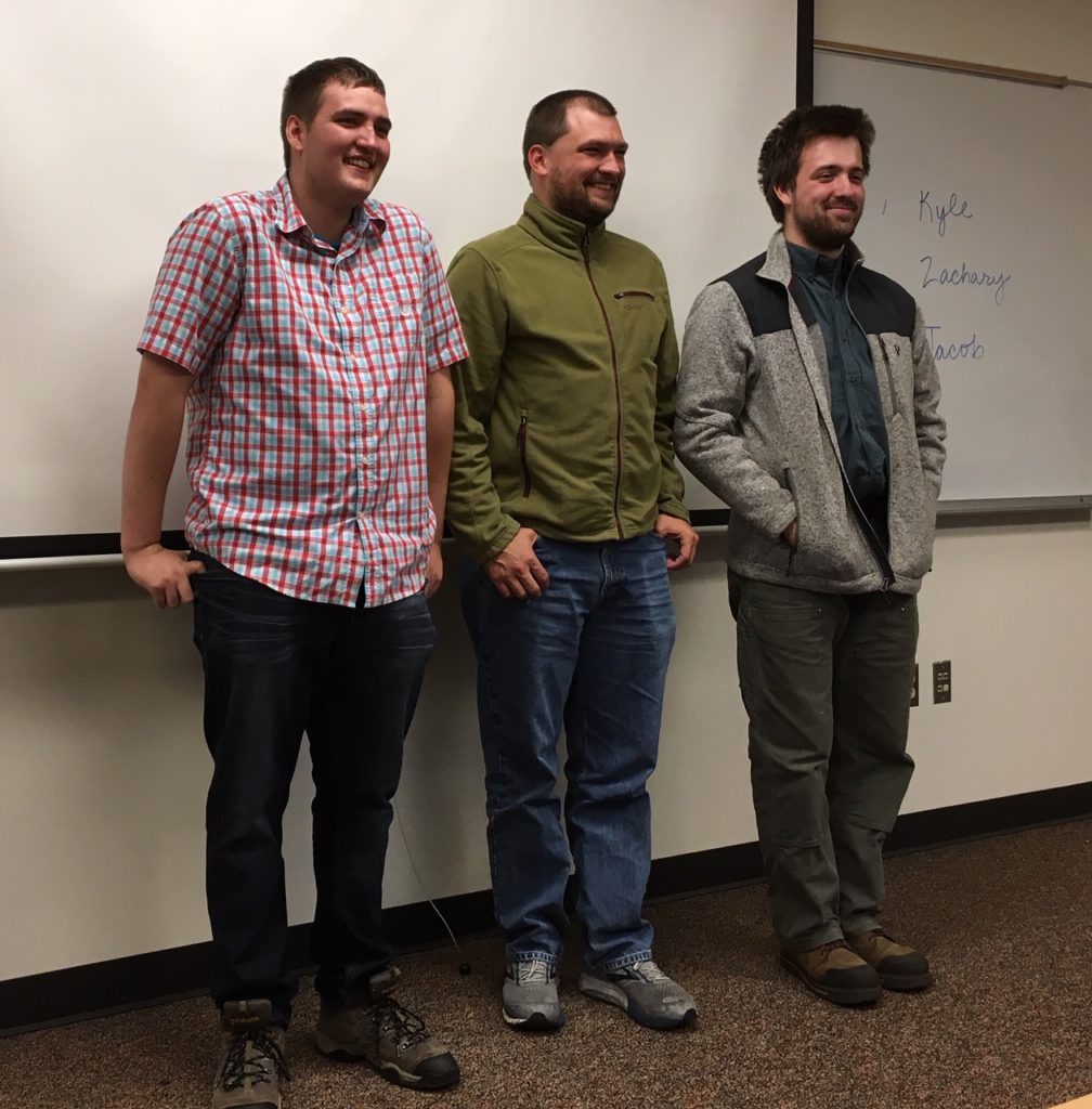 three young adults stand at the front of a college classroom