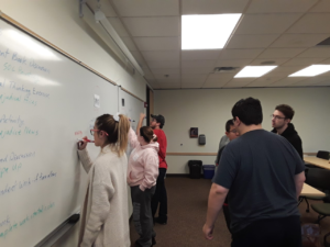 group of students work at white board in class