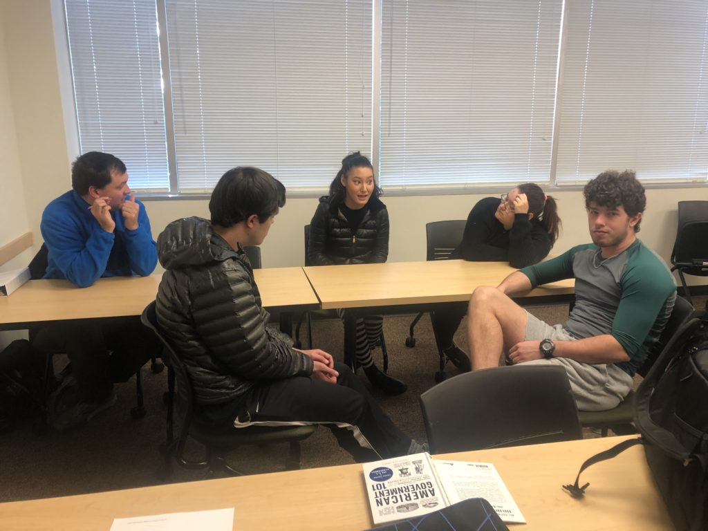 a group of 5 male and female students discuss politics around a table