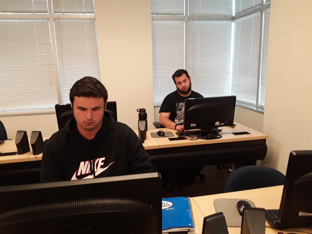 two young adults work at computers