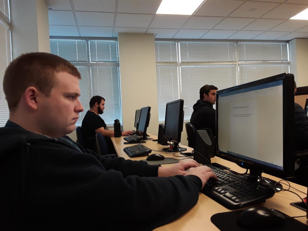 three young adult men work on computers