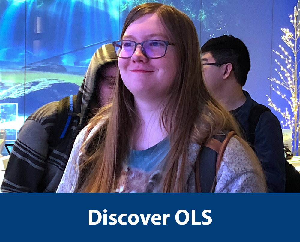 "a female OLS student stands in the Microsoft Visitor Center on a community activity for the OLS computers course with text ""Discover OLS"" a the bottom of the photo. Click photo to be redirected to the Program Overview webpage."