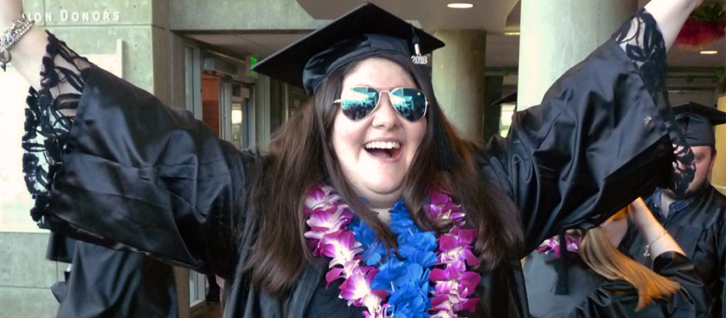 OLS student in camp and gown celebrates at graduation with a big smile and hands in the air
