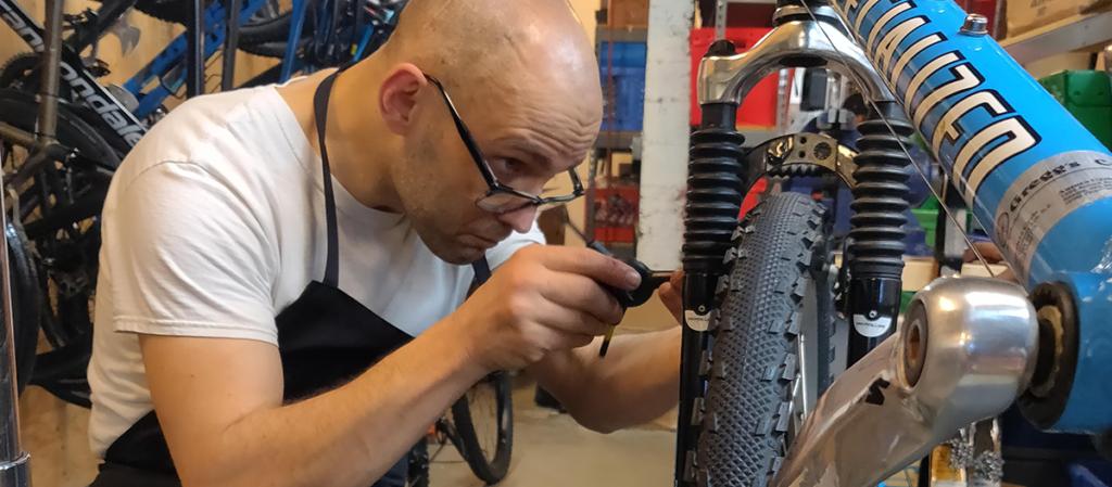 An OLS student works repairing a bike for their OLS internship