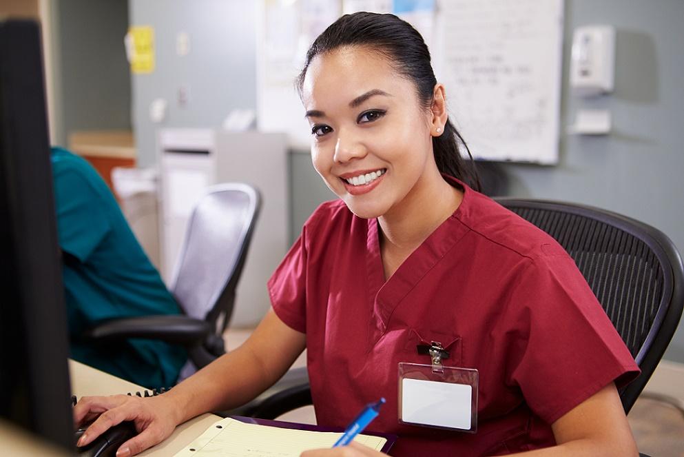Healthcare worker sitting at desk smiling