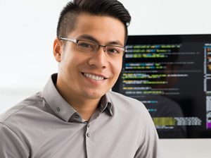 Student posed in front of computer with code on screen