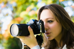 Young woman looking through digital camera