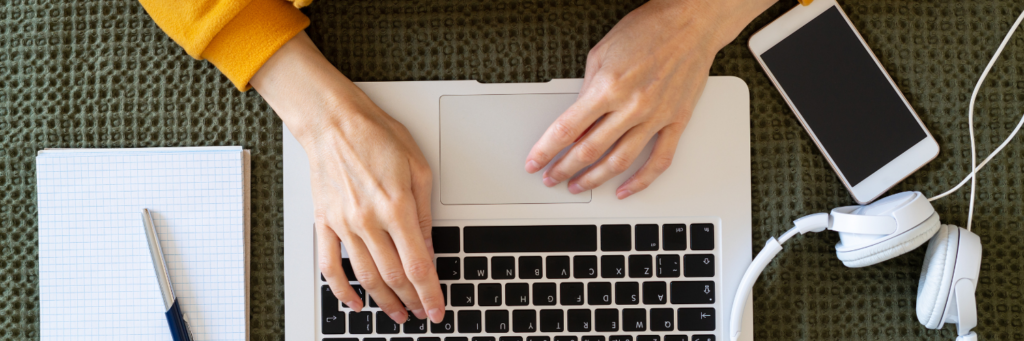 Image of person's hands working on a laptop with a mobile phone, headphones, pen and notebook nearby.