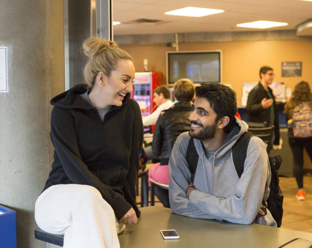 Two students looking at each other and smiling in the Student Union building cafe.