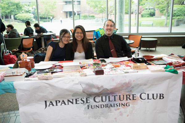 Two female students and one male student sitting at a booth raising awareness for the Japanese Culture Club at Bellevue College