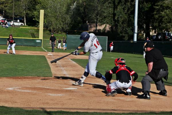 Bellevue College baseball player hitting a baseball in a game.
