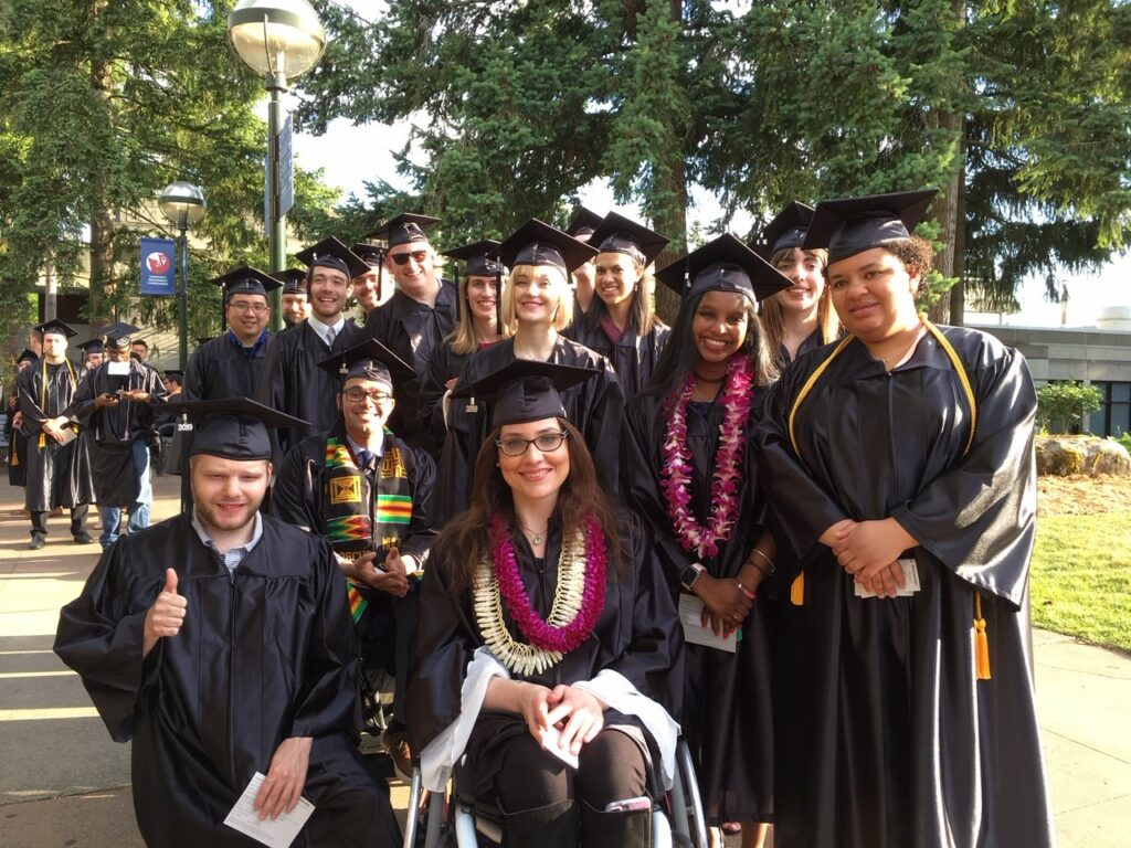 Diverse group of Bellevue College Occupational and Life Skills students wearing graduation caps and gowns at an outdoors commencement ceremony.