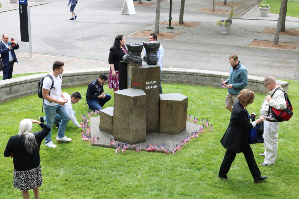 Students placing American flags around memorial sculpture for veterans on Bellevue College campus.