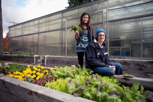 Male and female student sitting outside the Bellevue College greenhouse.