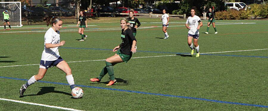 A B ellevue College women's soccer player kicks the ball in a match