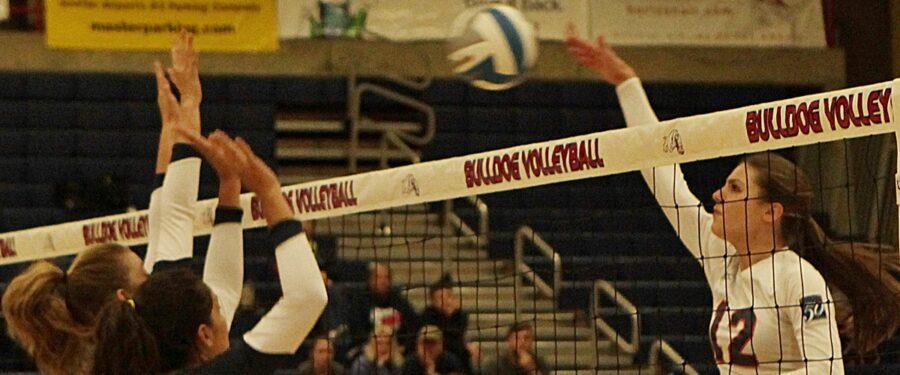 A Bellevue College vollyeball player hits the ball at the net
