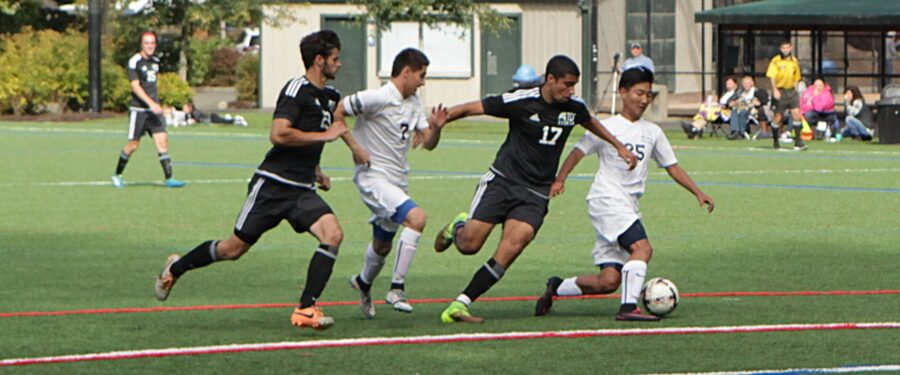 Two BC players battle against two Tacoma defenders in a men's soccer match