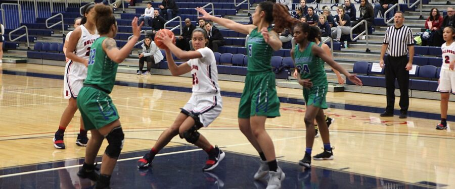 A BC women's basketball player is surrounded by Edmonds defenders