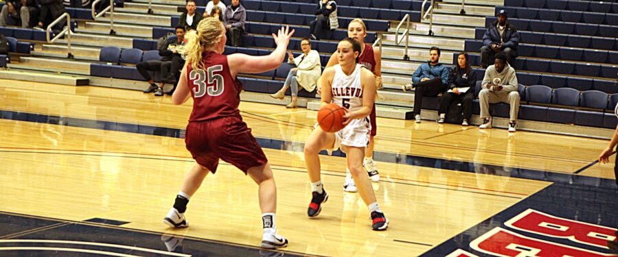 A BC women's basketball player holds the ball against a defender