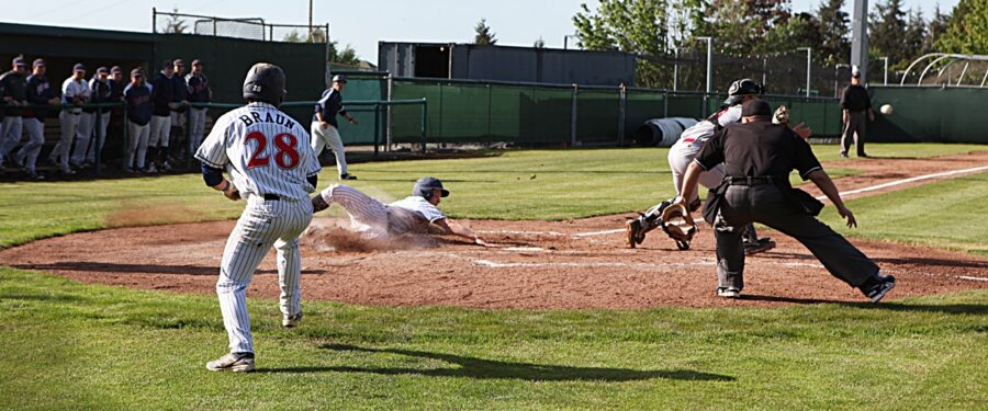 A Bellevue College runner slides safely at home plate against Everett