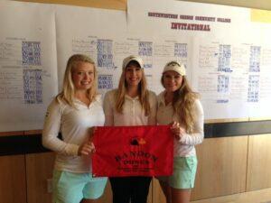 The BC women's golf team holding the SW Oregon Invite championship banner.
