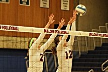 Two Bellevue College volleyball players attempt to block a shot