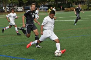 A BC men's soccer player kicks the ball vs. Tacoma