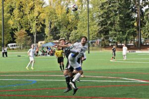 A BC men's soccer player battles a Tacoma player for the ball
