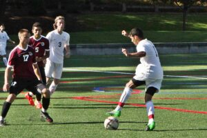 A BC men's soccer player kicks the ball against Pierce
