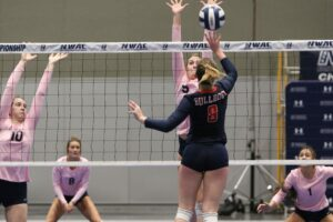 A BC player taps the ball over the net
