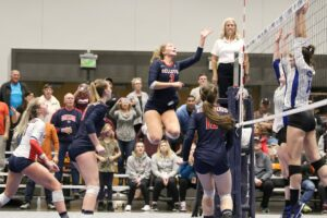 A BC player soars above the net after a shot