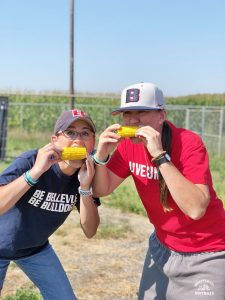 BC coach Leah Francis and a player eating corn on the cob