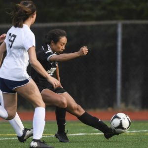 Juneau-Douglas' Malia Miller, right, kicks a ball while defended by an opponent