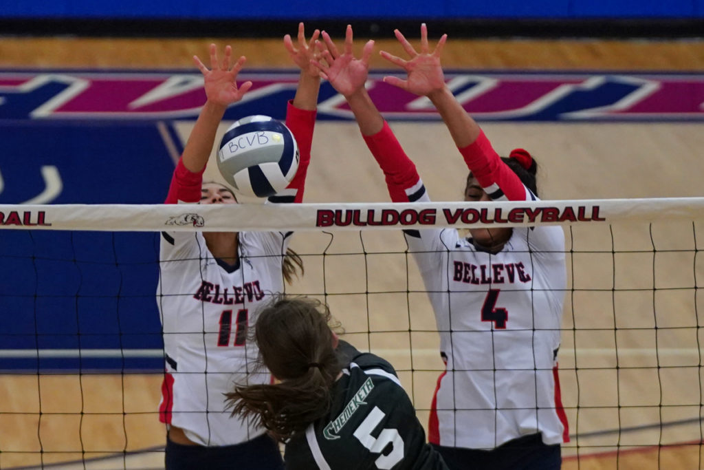 Two Bellevue volleyball players go up for a block