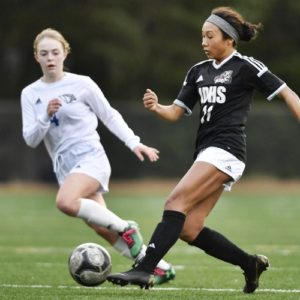Juneau-Douglas' Malia Miller, right, moves the ball against a defender in a high school soccer match