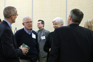 Ernie Woods speaking with other attendees