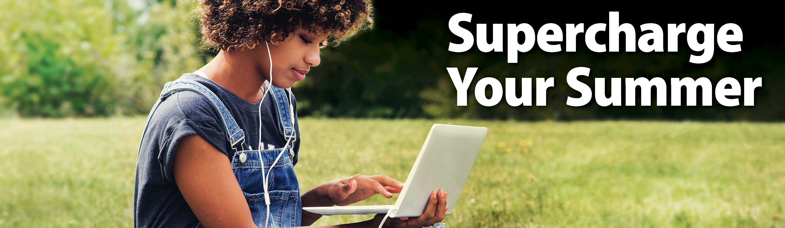 Supercharge Your Summer. Black female student working on laptop outside on the grass on a sunny day.
