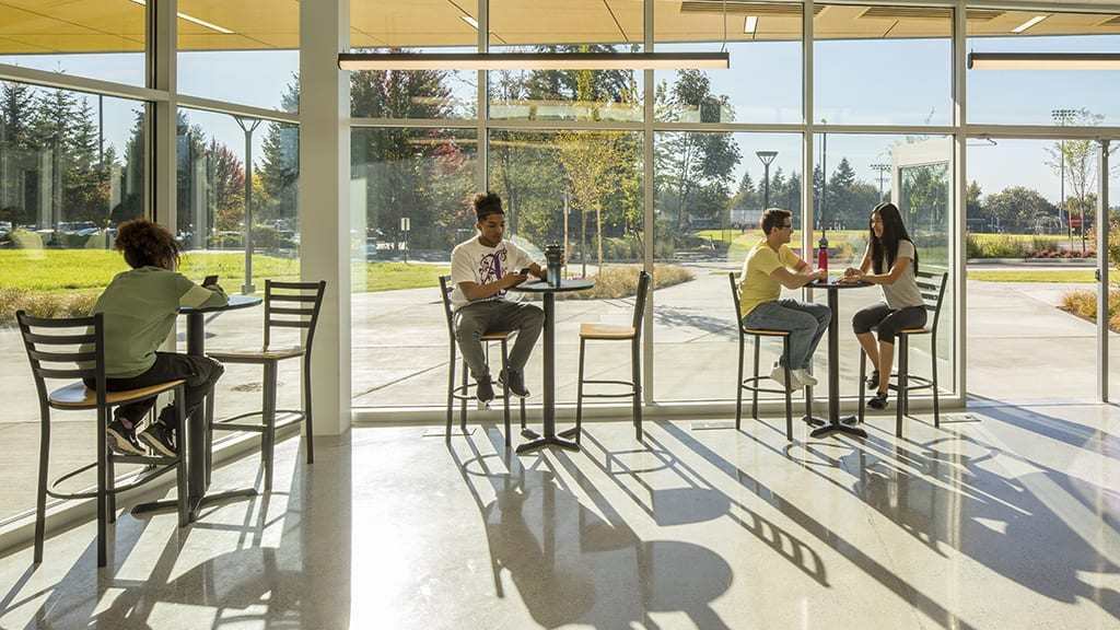Students sitting in windows of the cafe looking out on patio.