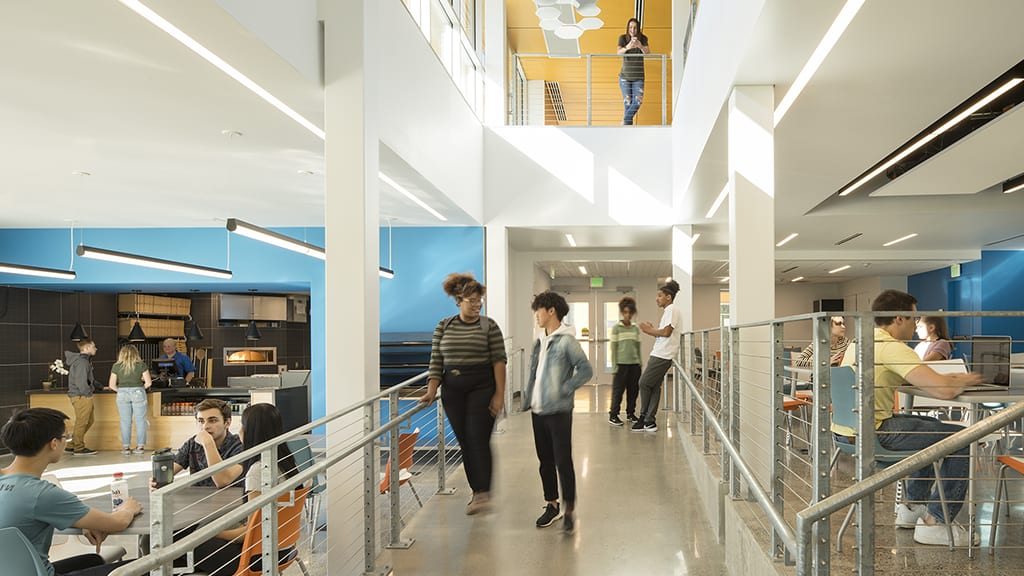 Students in dining area with second floor overlook.