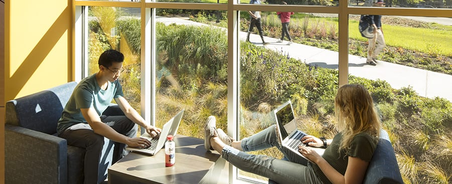 Students with their laptops sitting in a corner window.
