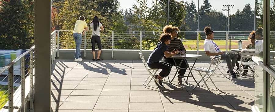 Students enjoying late sun on the second floor west balcony.