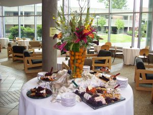 Catering spread with center piece and food around a table covered in white linen