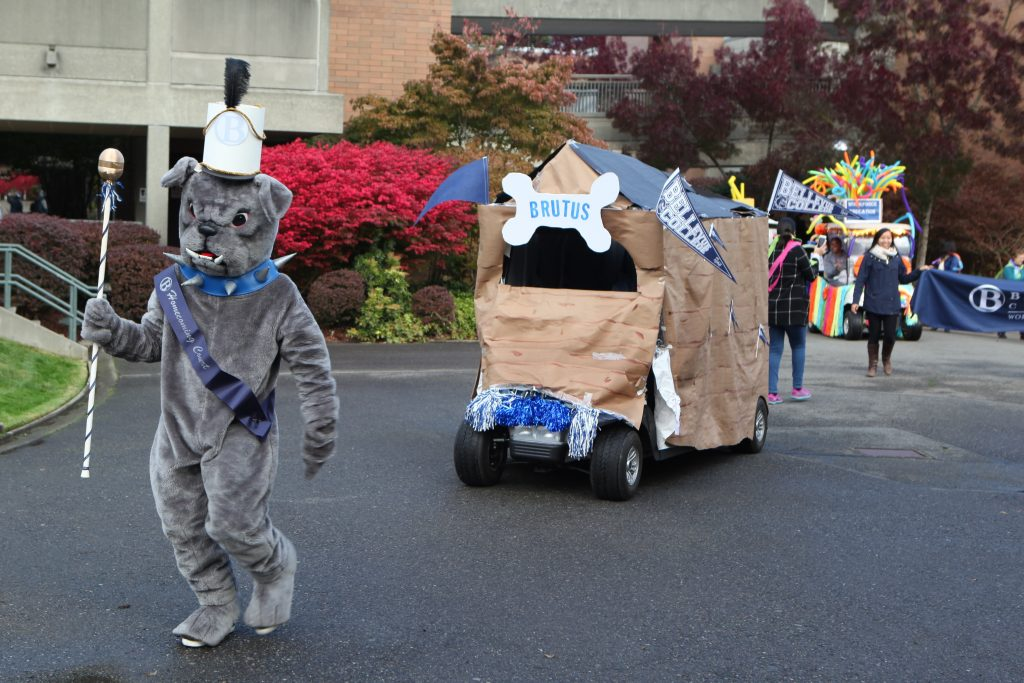 A decorated golf cart being led by Bellevue College mascot Brutus
