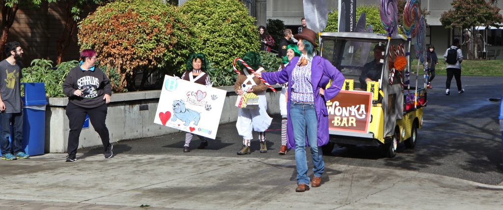 Perons dressed as Willy Wonka leading golf cart across Bellevue College