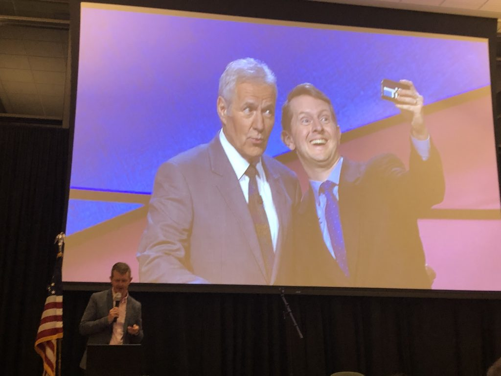 Ken Jenning's displaying a picture of himself with Alex Trebek