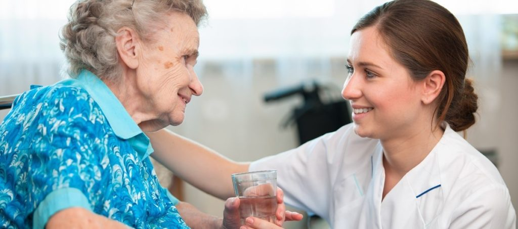 nurse smiling while handing a glass of water to an elderly patient
