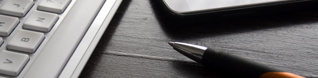 laptop, cellphone and orange pen on a wooden desk