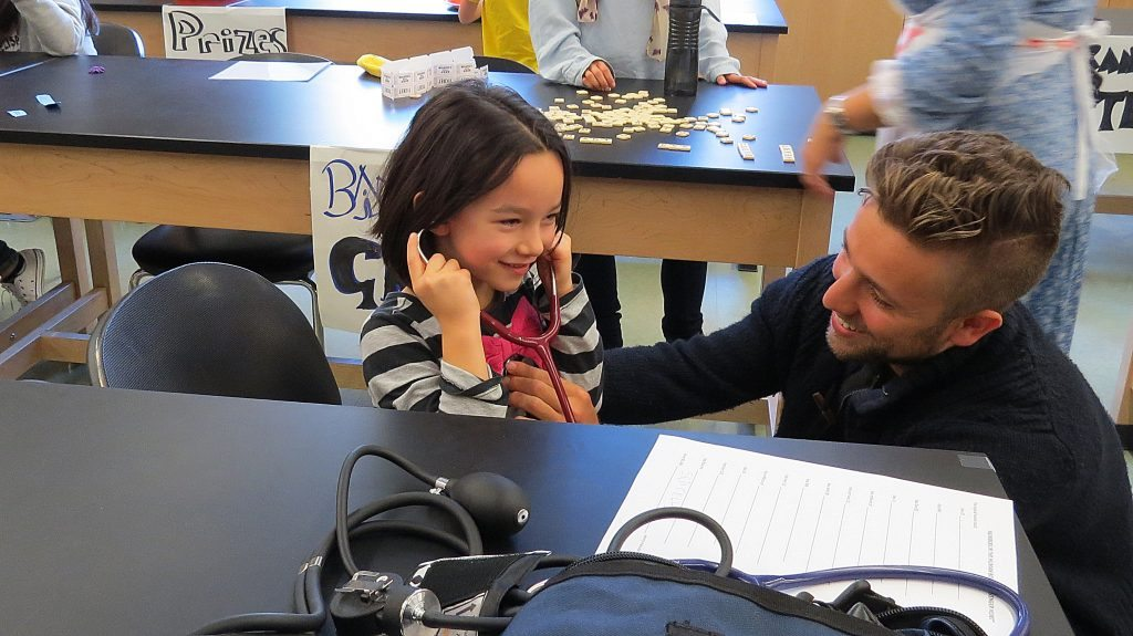 Picture of 5 year old with stethoscope working with Anatomy and Physiology student volunteer